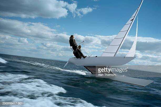 couple sailing catamaran - catamaran stock photos and pictures
