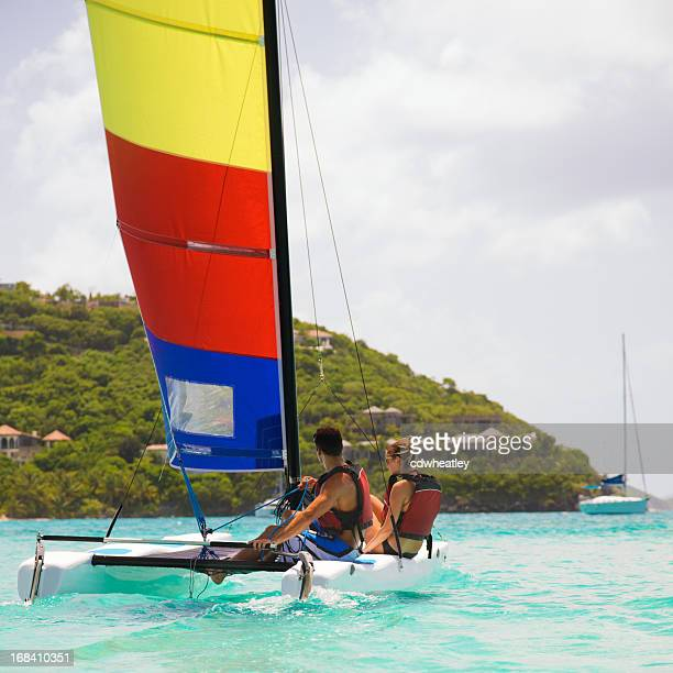 couple sailing on a catamaran in the caribbean - catamaran sailing stock photos and pictures