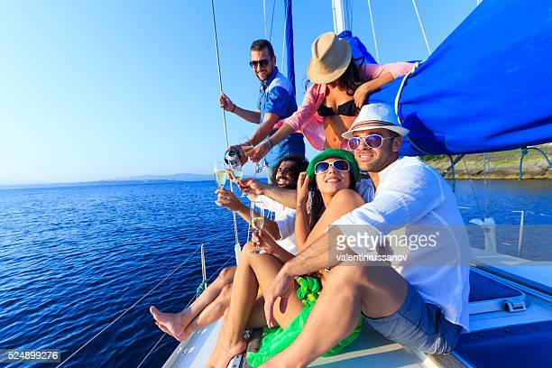Couple sailing with friends and having fun on sailboat