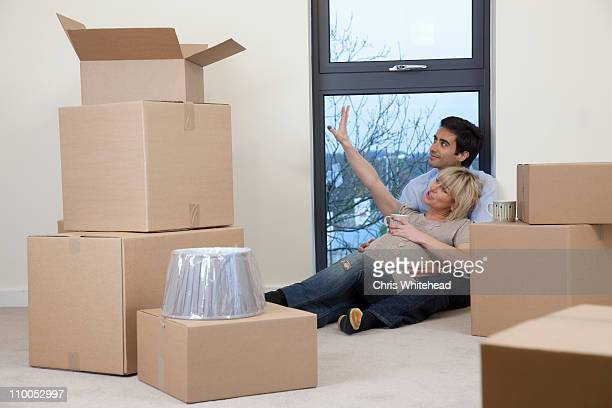 Couple sat amongst boxes in apartment