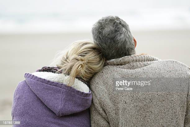 couple sat on beach in winter looking out to sea - 45 49 years stock pictures, royalty-free photos & images