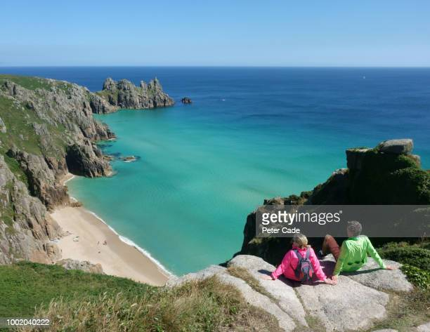couple sat on clifftop looking down at beach - cornwall england stock pictures, royalty-free photos & images