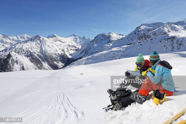 couple sat on snowy mountain - black hat stock pictures, royalty-free photos & images