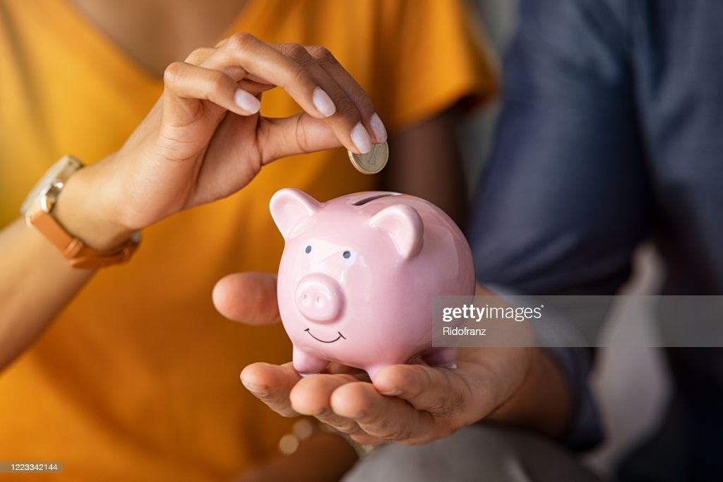 Couple saving money in piggybank : Stock Photo