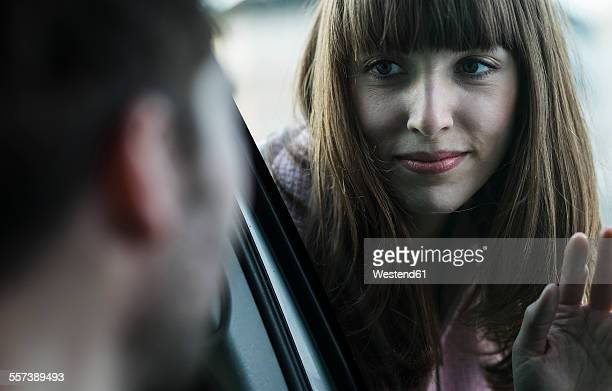 Couple saying farewell through windscreen