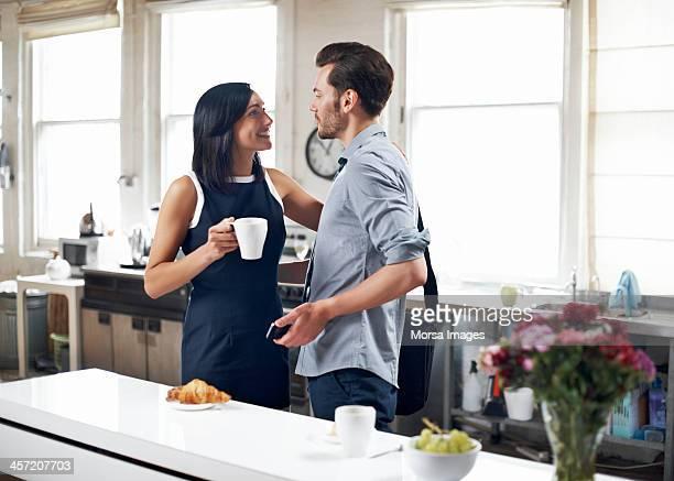 Couple saying goodbye in kitchen