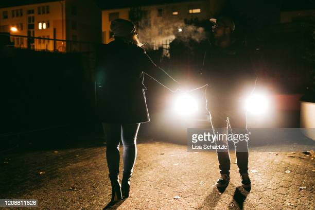 couple says goodbye to each other in the night - lisa strain stock pictures, royalty-free photos & images