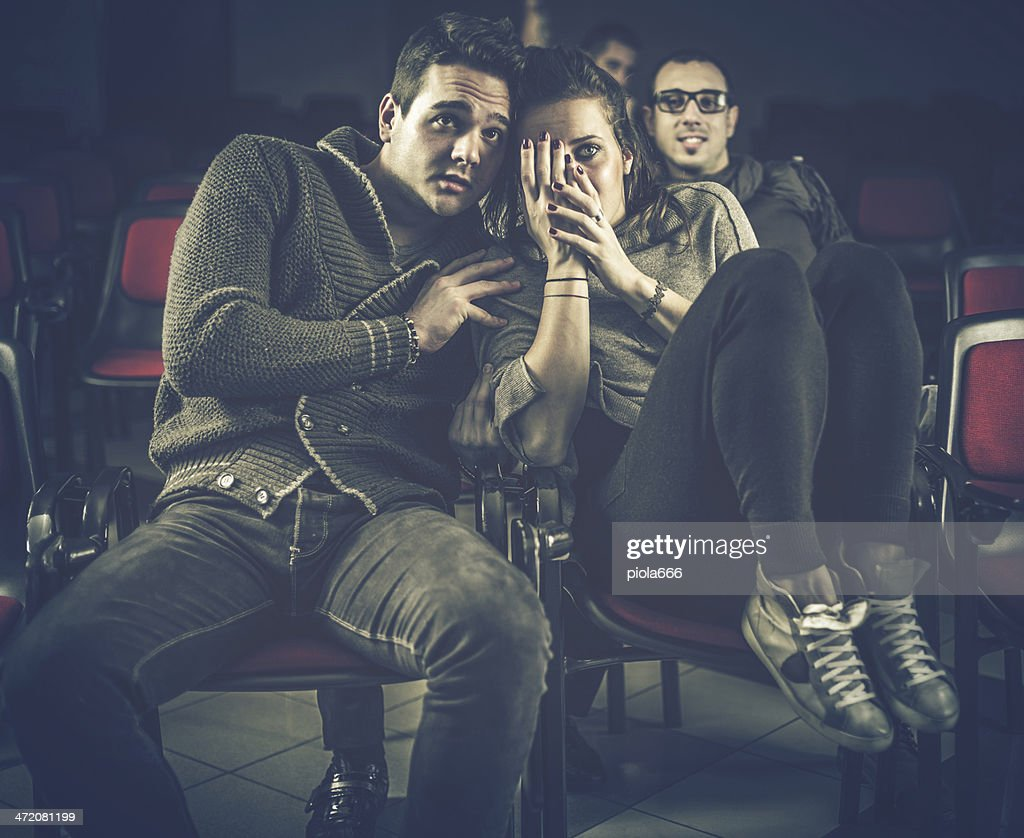 Couple scared at the cinema, watching horror movie : Stock Photo