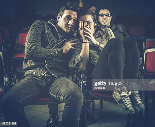 couple scared at the cinema, watching horror movie - horror movie stock photos and pictures