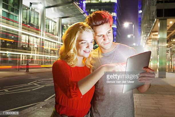 Couple searching on digital tablet in city.