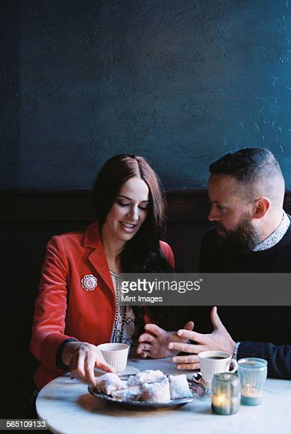 A couple seated side by side at a cafe table.