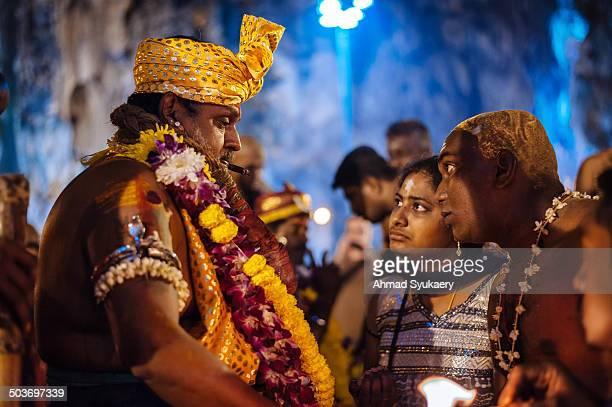 Couple seeking counsel from a Hindu priest during Thaipusam Festival at Batu Caves temple, Kuala Lumpur, Malaysia