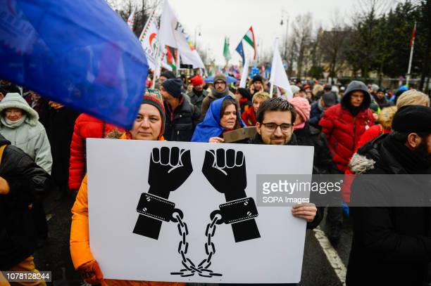 A couple seen holding a placard with chained hands during a protest in Heroes Square against the enactment of a recent labor law also called the...