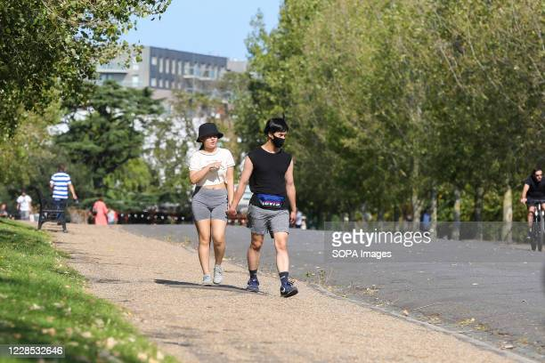 Couple seen walking in Finsbury Park, north London on a warm and sunny afternoon as mini heatwave hits the city.