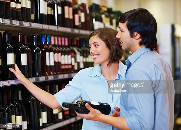 Couple selecting a wine bottle at the supermarket