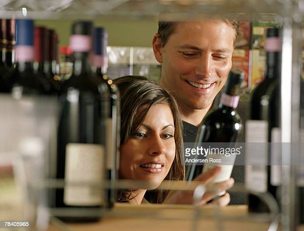 Couple selecting bottle at wine shop
