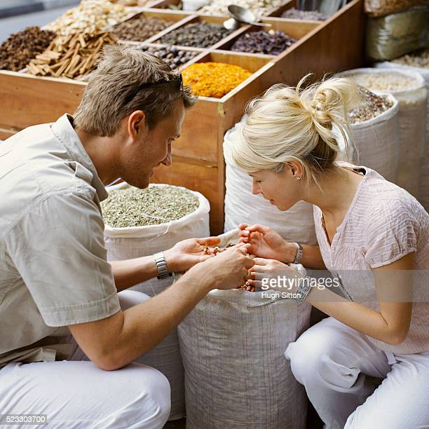 couple selecting spice at market stall - hugh sitton stock pictures, royalty-free photos & images