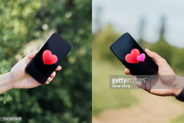 couple sending love messages using smartphone - love stock pictures, royalty-free photos & images