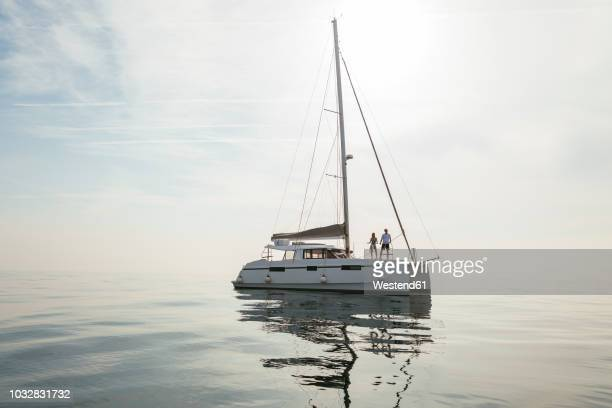 couple setting off for a sailing trip on a catamaran - catamaran stock photos and pictures