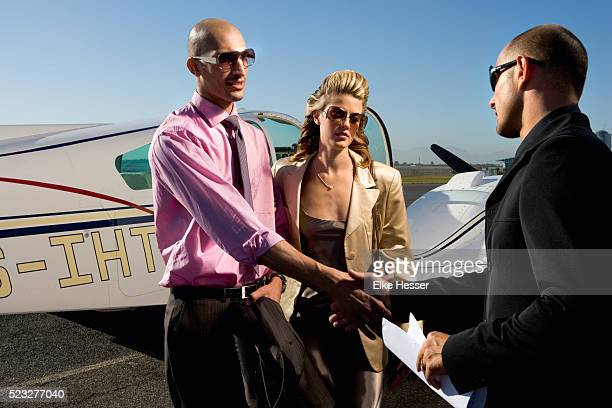couple shaking hands with a young man in front of airplane - best sunglasses for bald men stock pictures, royalty-free photos & images