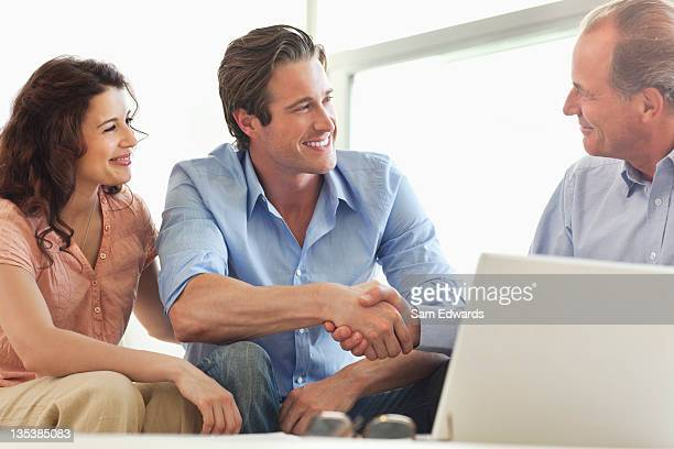 couple shaking hands with financial advisor - deal england stock photos and pictures