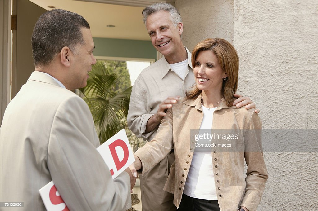 Couple shaking hands with realtor at new home : Stockfoto
