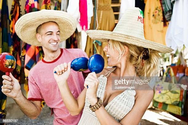 couple shaking maracas in store - mexican hat stock pictures, royalty-free photos & images