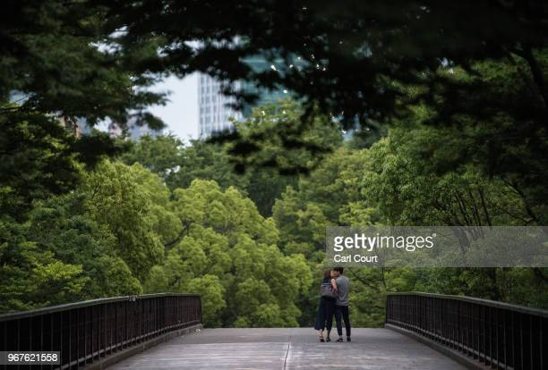 Couple share a kiss as they cross a footbridge in Yoyogi Park on June 5, 2018 in Tokyo, Japan.
