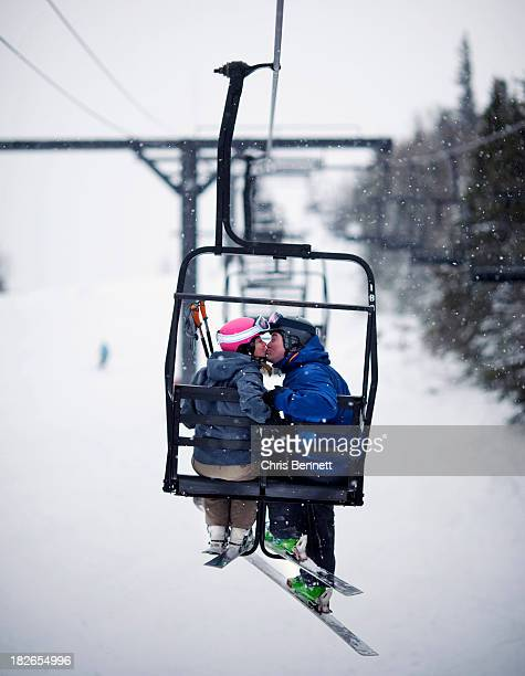A couple share a kiss on a chairlift in softly falling snow.