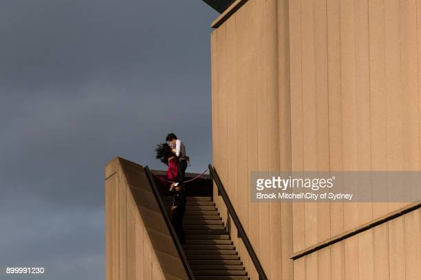 A couple share a kiss on the Opera House steps on New Year's Eve on Sydney Harbour on December 31 2017 in Sydney Australia