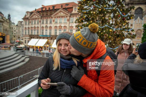 カップルはプラハのクリスマスマーケットで一瞬を共有しています。