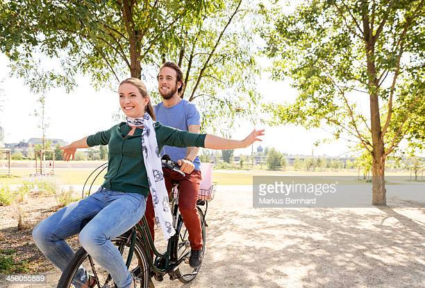Couple share a ride on their bicycle.