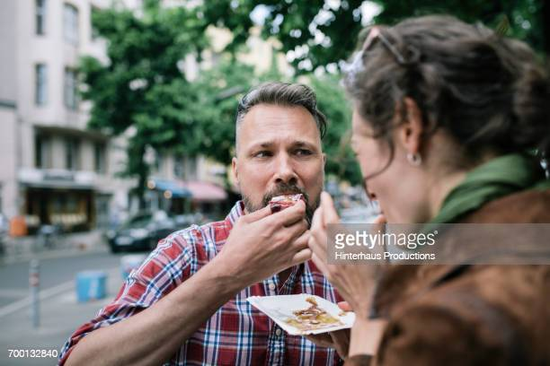 couple share streetfood - man eating woman out stock photos and pictures