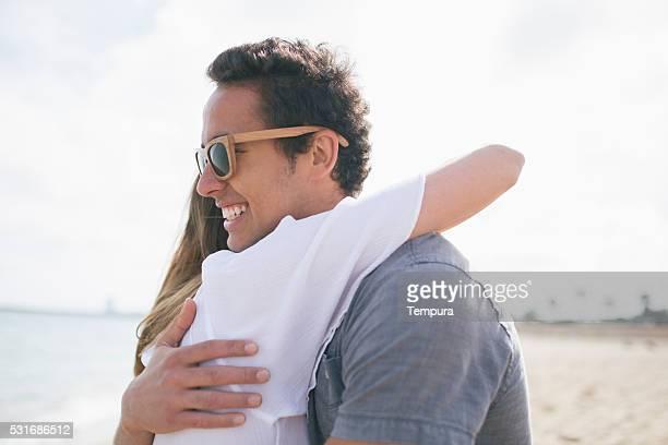 Paar teilen einen großen Umarmen in den Strand.