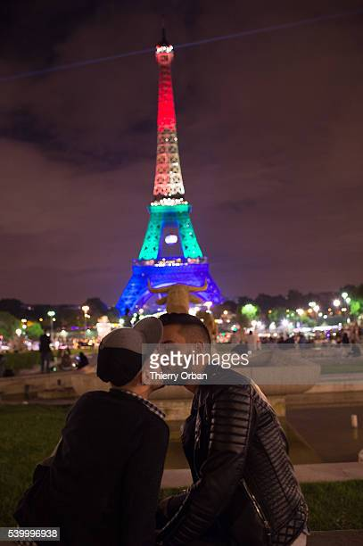 Couple shares a kiss in front of the Eiffel tower, lit with rainbow colors in tribute to the victims of the Pulse Nightclub shooting, June 13, 2016...