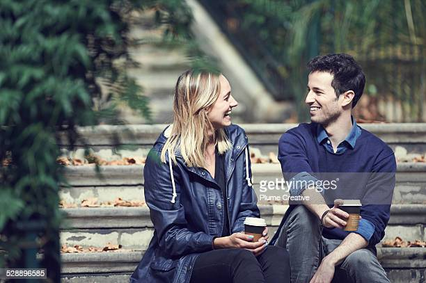 Couple sharing a coffee on stairs
