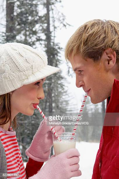 Couple sharing a glass of milk outdoors