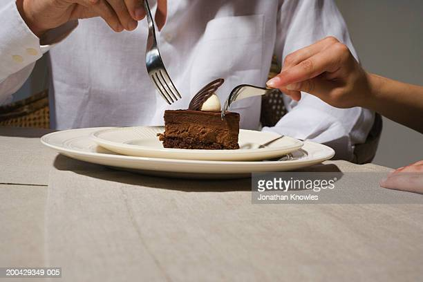 Couple sharing chocolate dessert at dining table, close-up