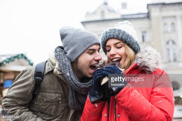 Couple sharing chocolate donut at Christmas market