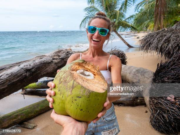 couple sharing coconut on tropical beach - costa rica stock pictures, royalty-free photos & images