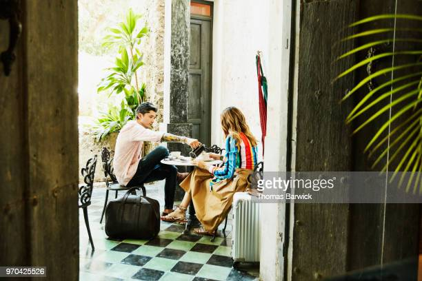 Couple sharing coffee while sitting at outdoor cafe during vacation