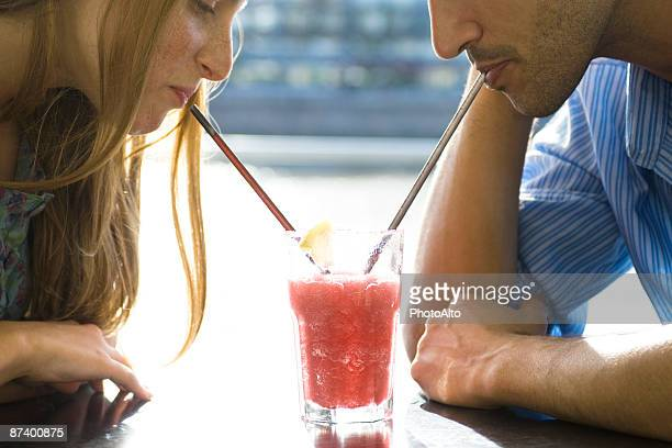 Couple sharing cool drink, cropped