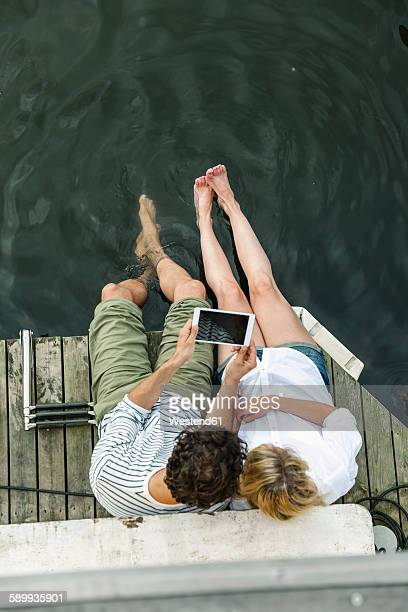 Couple sharing digital tablet at the water