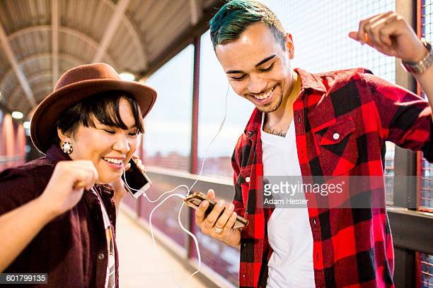 Couple sharing earphones to listen to music
