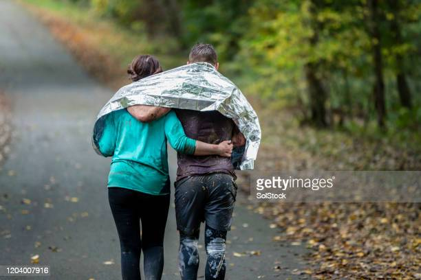 couple sharing foil blanket walking away from camera - charity benefit stock pictures, royalty-free photos & images
