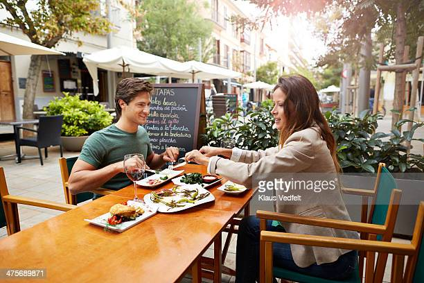 couple sharing food at restaurant - klaus vedfelt mallorca stock pictures, royalty-free photos & images