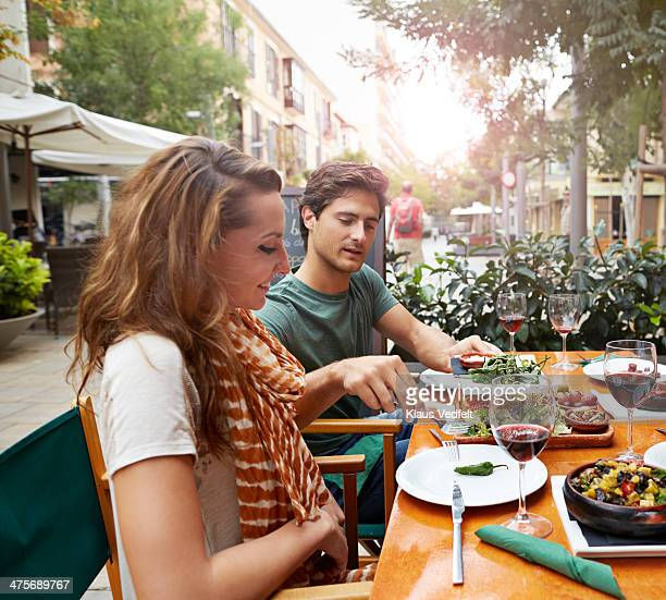 couple sharing food at tapas restaurant - klaus vedfelt mallorca stock pictures, royalty-free photos & images