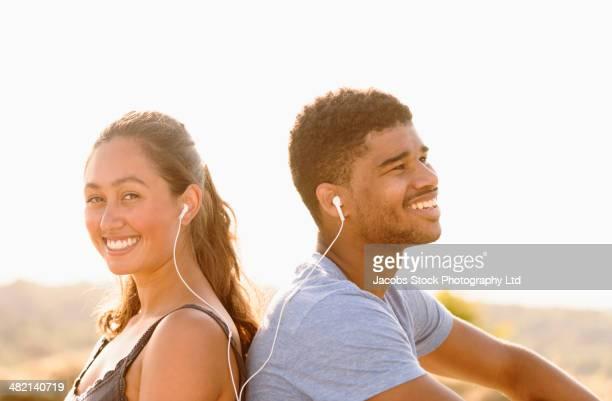 Couple sharing headphones outdoors
