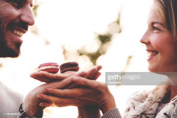 couple sharing macaroons - couple chocolate stock pictures, royalty-free photos & images