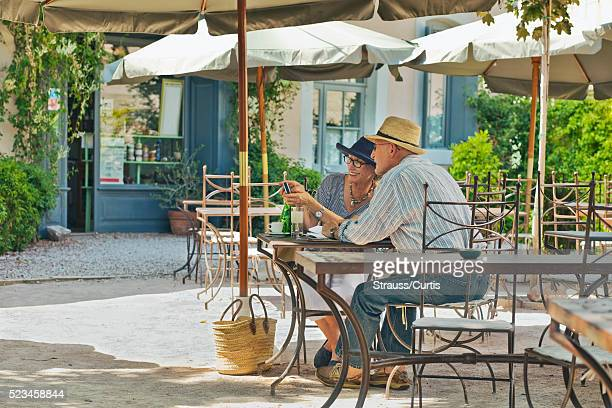 couple sharing photos on digital camera in outdoor cafe. - guy carcassonne photos et images de collection